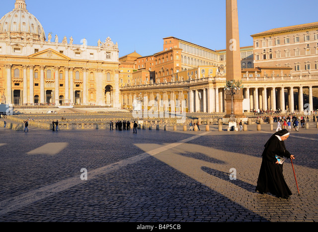 A Catholic nun with cane crossing St Peters Square in early morning. Stock Photo
