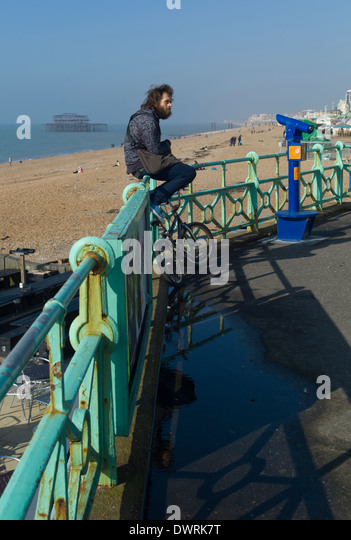 Soaking up the spring sunshine on the Beach at Brighton, with the West Pier in the background - Stock Image