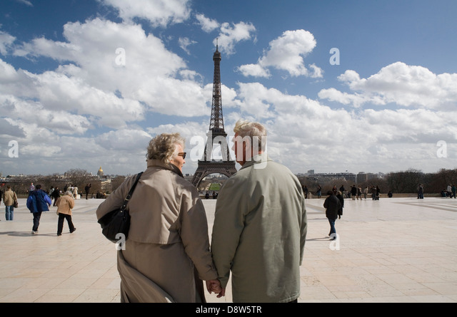 Retired couple (70s) holding hands and talking, Eiffel Tower in background. Paris, France - Stock Image