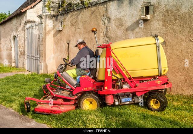 Motor powered sit-on Ferrari grass mower - France. - Stock Image