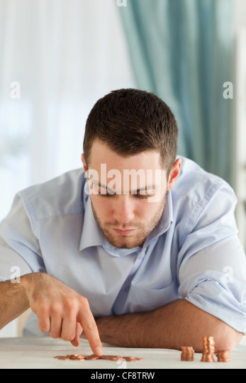 Businessman counting change - Stock Image