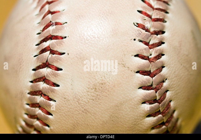 Close up of the red stitching on a baseball - Stock Image