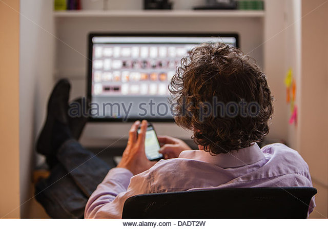 Male with smartphone in front of computer screen - Stock Image
