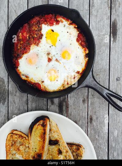 Tomato and eggs cooked in wood fire oven - Stock Image