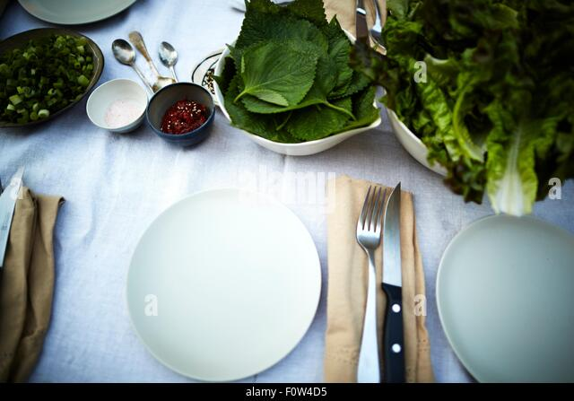 Table settings and fresh vegetable on table - Stock Image