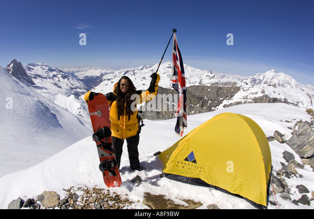 Female Mountaineer on summit of mountain with Union Jack and Snowboard - Stock Image