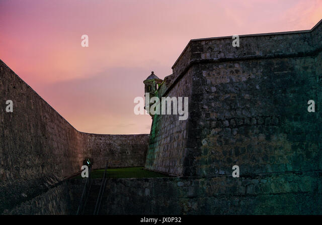 Stone walls and a dry moat surrounding the Fuerte de San Miguel or Fort St Michael in Campeche, Mexico. Turret or - Stock Image