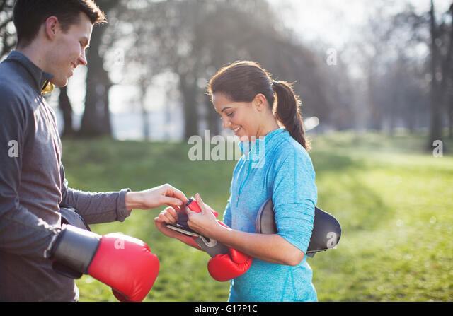 Young man and woman putting on boxing gloves for training in park - Stock Image
