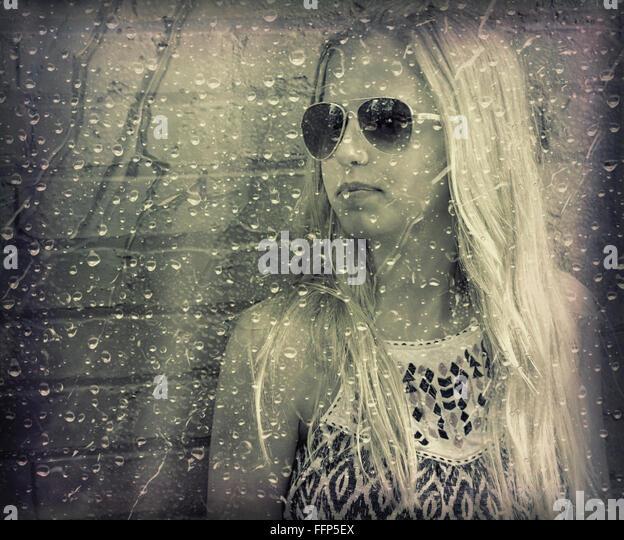 Teenage girl wearing aviator sunglasses with raindrops on window overlay. - Stock-Bilder