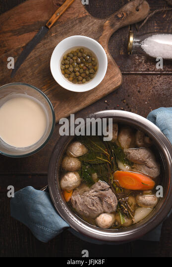 Meat broth , onion , mushrooms , carrots and capers on the wooden table top view - Stock Image