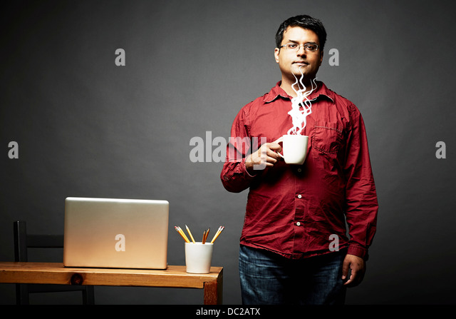 Man holding cup of steaming hot beverage - Stock Image