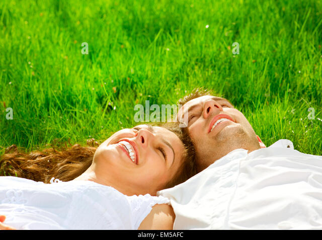 Happy Smiling Couple Relaxing on Green Grass. Park - Stock Image