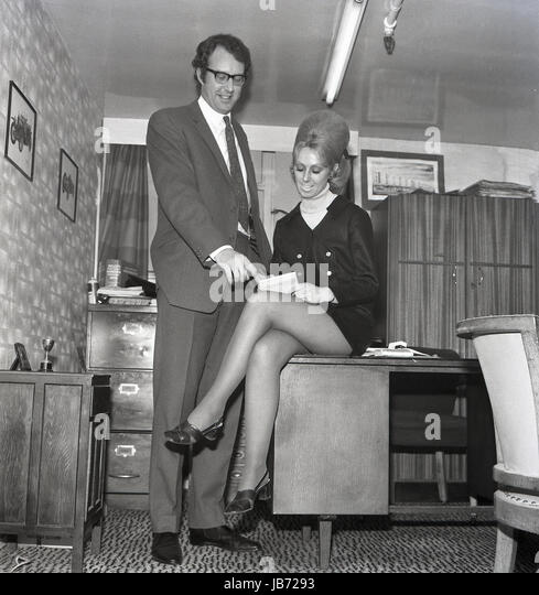 1970s, historical, a secretary wearing a mini-skirt sits on the edge of a her boss's desk as she takes notes - Stock Image