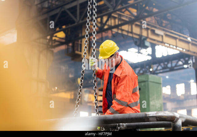 Steel worker fastening chain in factory - Stock Image
