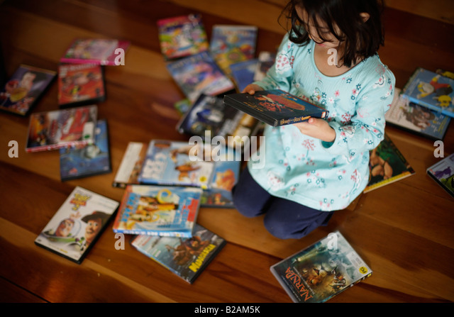 Five year old girl spends time choosing a DVD to watch in the afternoon - Stock Image