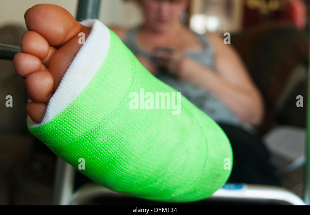 A woman with a broken ankle, elevating her foot and reading her cell phone. - Stock Image