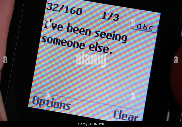 Text message on a mobile phone stating 'I've been seeing someone else.' - Stock Image