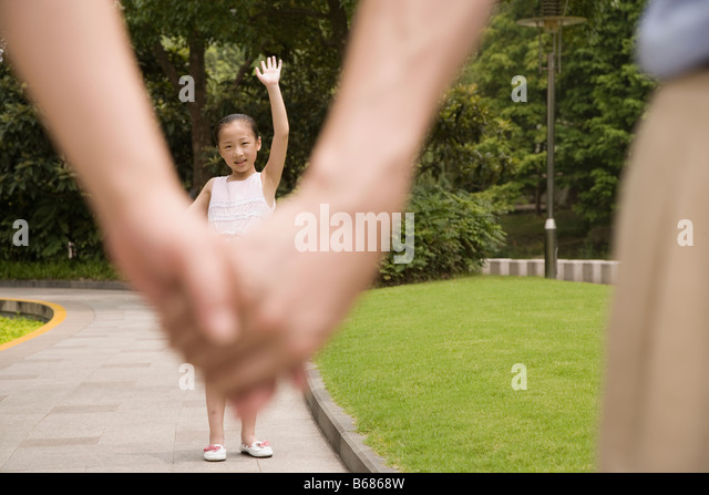 Girl standing in a garden and waving her hand to her parents - Stock Image