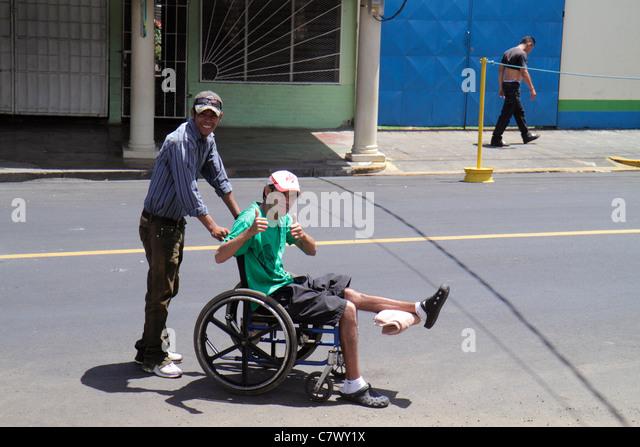 Nicaragua Managua street scene pedestrian crossing wheelchair Hispanic man pushing - Stock Image