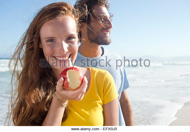 Smiling couple on sunny beach, with woman holding an apple with a bite out of it - Stock-Bilder
