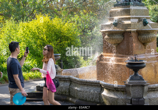 Sydney Australia NSW New South Wales Royal Botanic Gardens public fountain Asian man woman couple smartphone - Stock Image