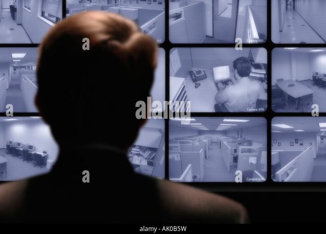 Video surveillance Man watching an employee work via a closed circuit video monitor - Stock Image