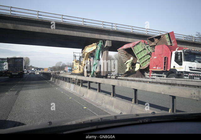 Driving along uk motorway with roadworks in central reservation at a bridge - Stock Image