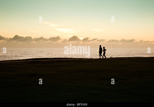 Two joggers in silhouette next to the ocean running with sun behind clouds in the horizon - Stock-Bilder