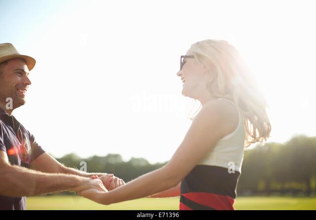 Couple swirling each other around in park - Stock-Bilder