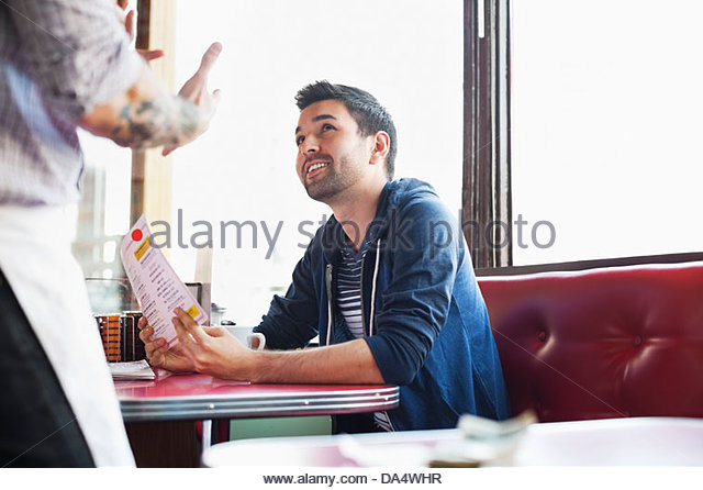 Male customer ordering food in diner - Stock Image