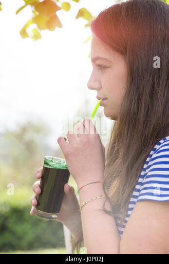 Girl tasting spirulina algae drink - Stock Image