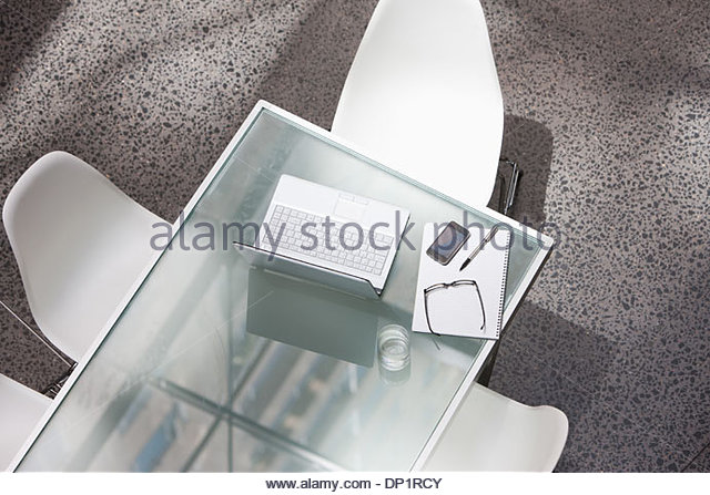 Laptop and water glass on conference table - Stock Image