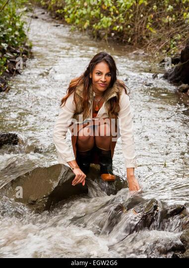 Woman kneeling in a creek. - Stock-Bilder