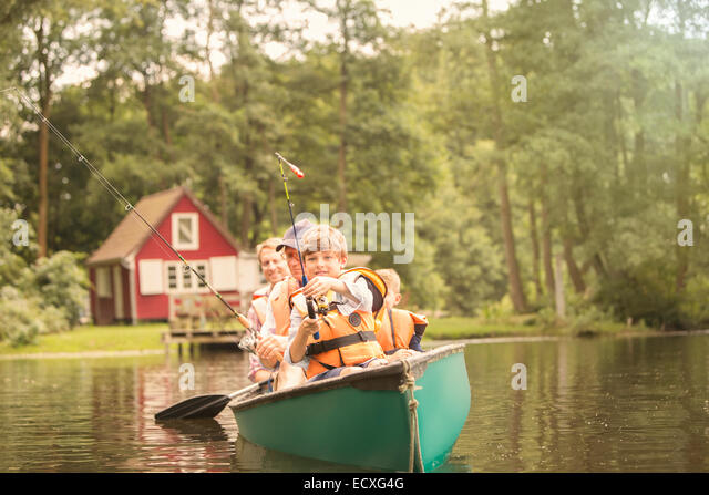 Father and sons fishing from canoe in lake - Stock Image