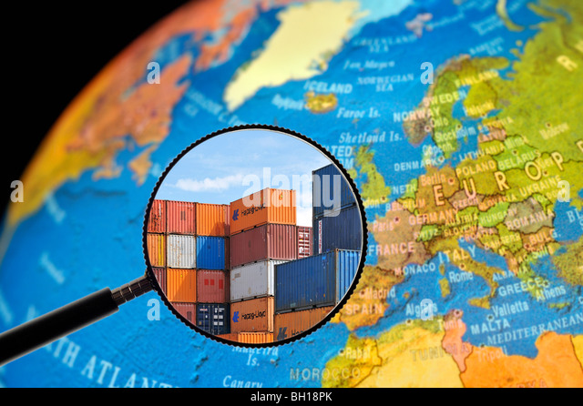 Piled up containers seen through magnifying glass held against illuminated terrestrial globe - Stock Image