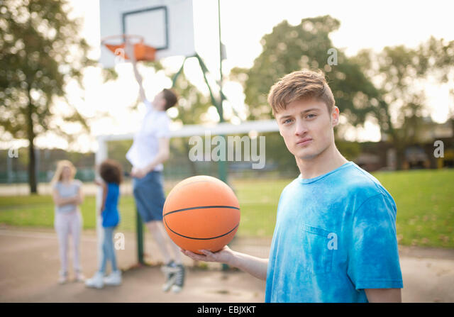 Portrait of young male basketball player holding basketball - Stock Image