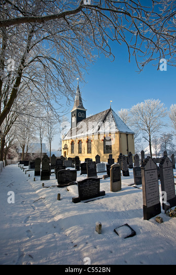 The Netherlands, Ferwoude, Church and graveyard in frost and snow. - Stock Image