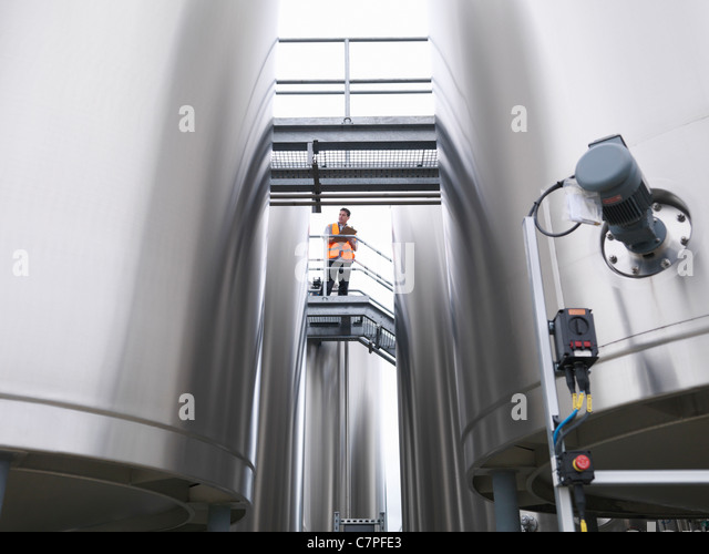 Worker checking tanks in bottling plant - Stock Image