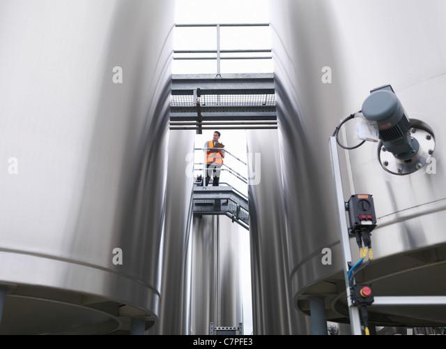 Worker checking tanks in bottling plant - Stock Image