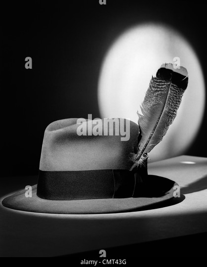 1940s FEDORA HAT WITH FEATHER IN BAND IN SPOTLIGHT SYMBOLIC FEATHER IN YOUR CAP - Stock Image