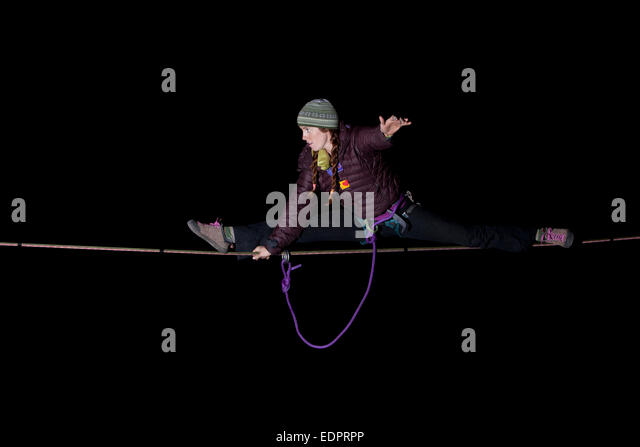 Professional highliner Hayley Ashburn in winter clothing doing the splits on a highline in the dark - Stock Image