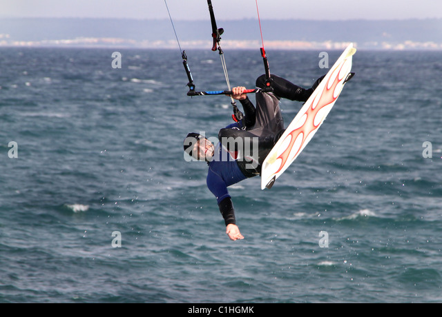 Man doing tricks while kite wind surfing. - Stock Image