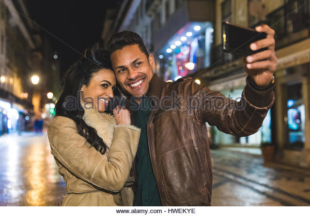 Couple in city at night, taking selfie, using smartphone, Lisbon, Portugal - Stock-Bilder