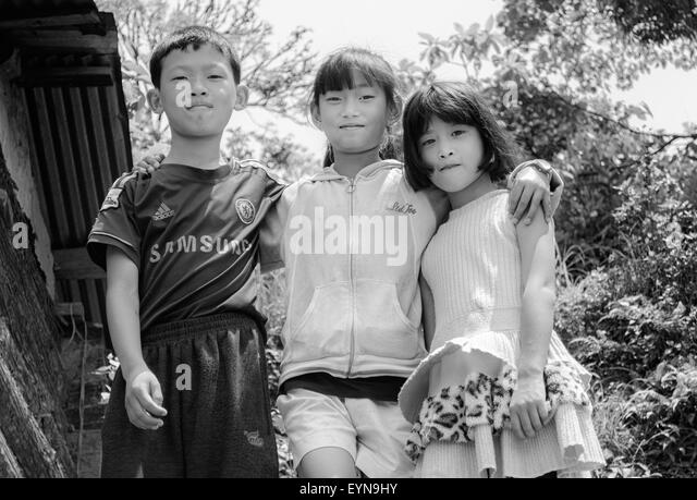 Three young children standing together with copy space - Stock Image