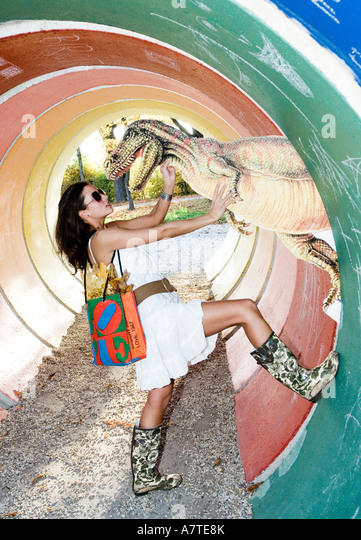 Side profile of young woman posing with reptile of dinosaur - Stock-Bilder
