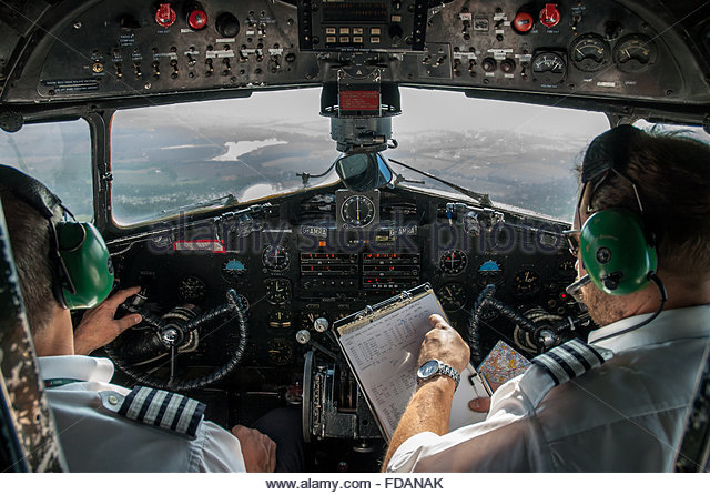 A cockpit view from inside a Douglas DC-3 in the air with its pilots working out its route . - Stock Image