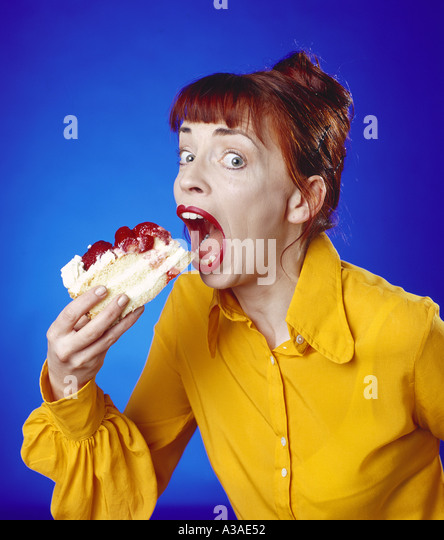 Girl eating cake - Stock Image