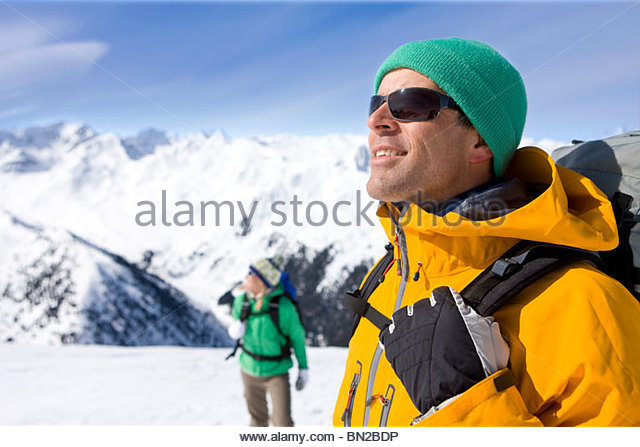 Couple with backpacks enjoying sunshine on snowy mountain - Stock Image