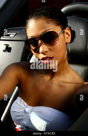 YOUNG WOMAN IN HER CAR WEARING SUNGLASSES MOODY LIGHTING - Stock Image