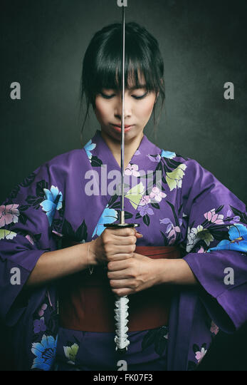 Samurai woman ready to fight with katana . Studio dark shot - Stock-Bilder
